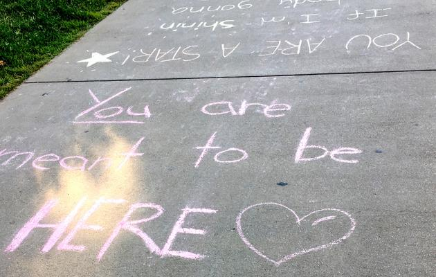 welcome message chalked on sidewalk